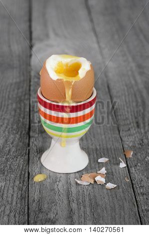 The soft-boiled egg in the stand, on a gray wooden background