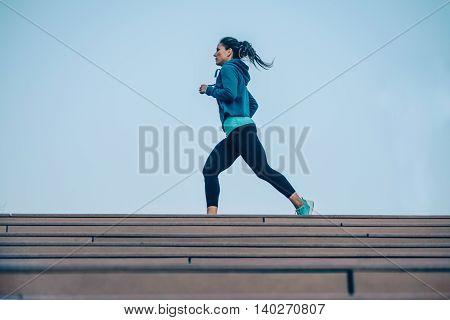 Woman jogging outdoors, toned image, horizontal image