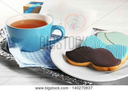 Happy Father's Day concept. Tasty cookies and cup of tea on wooden background