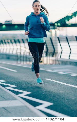 Woman running on riverside, toned image, vertical image