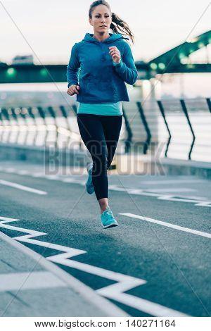 Woman running on riverside, toned image, vertical image