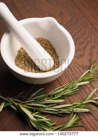 White porcelain mortar and pestle with rosemary on a wooden table