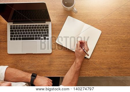 Man Writing Notes In Personal Notebook