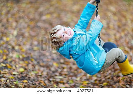 Little toddler child in blue rain jacket  and gumboots having fun with playing chain swing on playground on warm, autumn day, outdoors