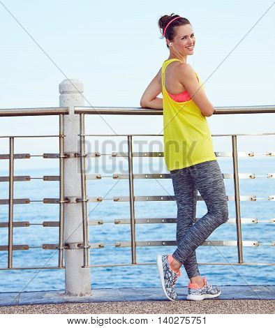 Full Length Portrait Of Happy Fit Woman Standing At Embankment
