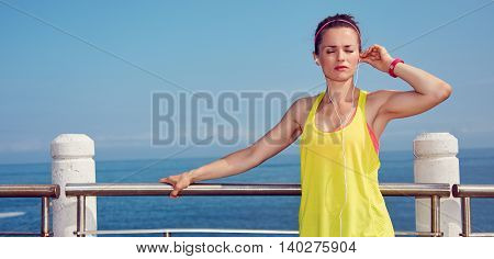 Relaxed Woman In Fitness Outfit Listening To Music At Embankment