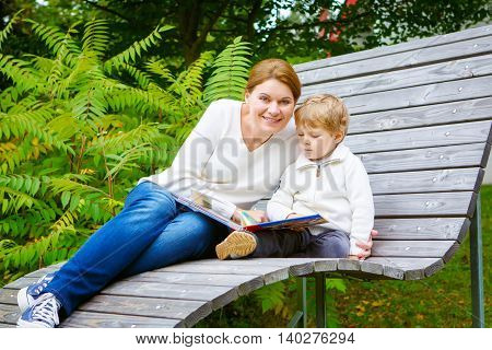 Little preschool boy and his mother sitting on bench in park and reading fairytale book together.