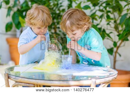 Two happy toddler boys having fun and making experiment with colorful soap bubbles and water, outdoors.
