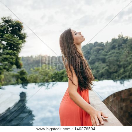 Attractive Woman Standing By A Railing Near Swimming Pool