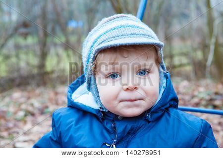 Portrait of little boy of one year in blue clothes outdoor