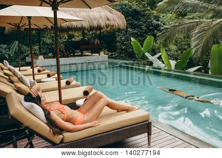 Woman At Poolside And Man Swimming