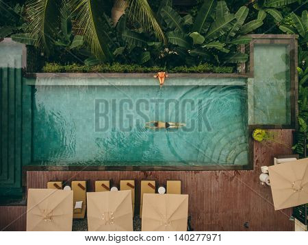Aerial shot of woman sitting at the poolside with man swimming in pool. Couple enjoying holiday at luxury resort.