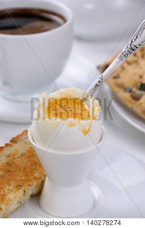 Soft-boiled egg with cup of coffee and toast for breakfast