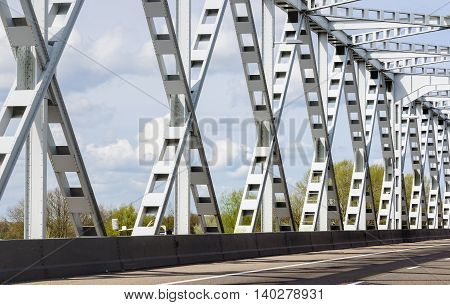 Closeup of a grey painted old Dutch riveted steel bridge on behalf of a road over a river.