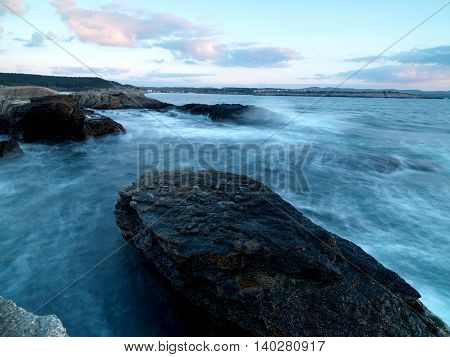 longexposure shoot to sea side with rocks and sea waves