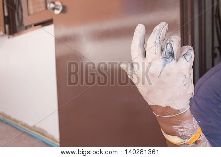 Painter mixing, hand with colors mix, painted home in the work