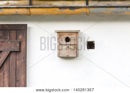 old simple nest box on a white wall