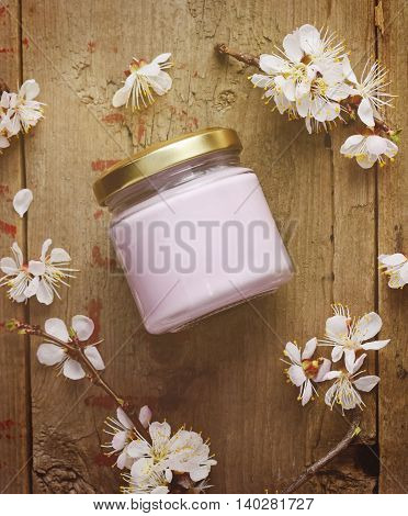 Organic cosmetic cream with apricot tree flowers on a wooden background. Vintage spa still life.