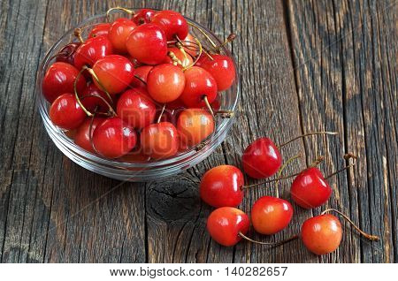 Ripe cherries in glass bowl on dark wooden background