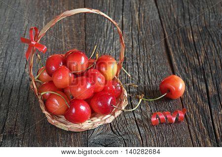 Cherries in small basket on dark wooden background