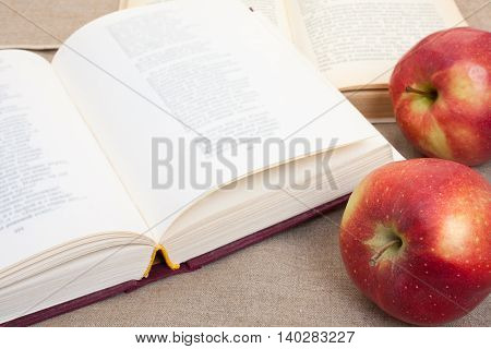 Composition With Red Apples And Opened Books On The Table, On The Decorative Linen Cloth.