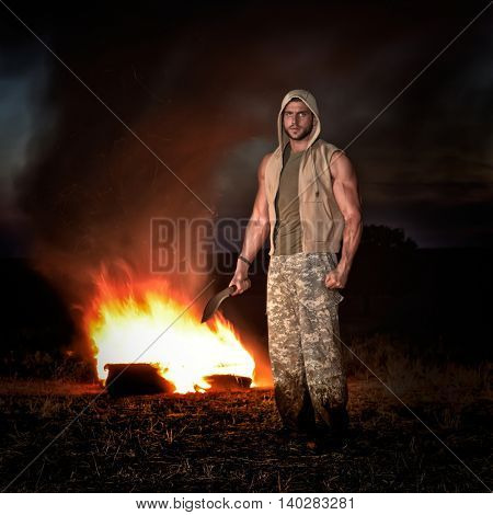 athletic young man outdoor at night holding knife
