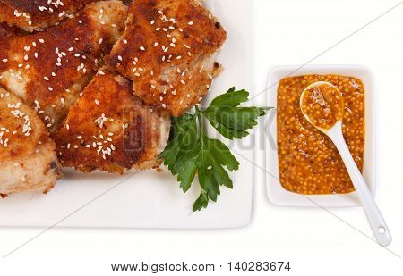 Chicken Fried In Breadcrumbs With Sesame Seeds, Parsley And Mustard. On A White Ceramic Dishes, Isol