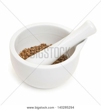 White Porcelain Set Mortar And Pestle With Coriander Grains. Isolated On White.