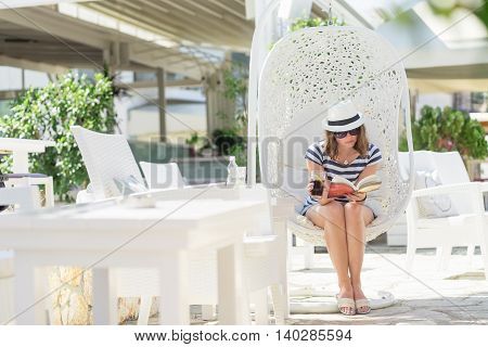 Young woman sitting in a woven rattan hanging basket with cushions enjoying the morning sun in an outdoor cafe by the sea reading a book and drinking juice