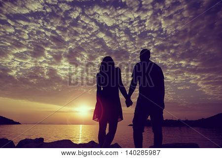 Silhouette of a couple in love holding hands and looking at a beautiful sunset in Syvota port Greece