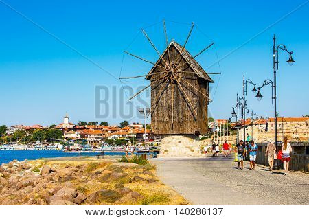 Nessebar, Bulgaria - July 25, 2016: Windmill, tourists and old town panorama in Nessebar or Nesebar in Bulgaria, Black sea