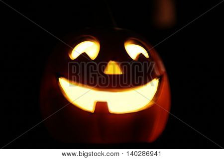 image of a smiling Halloween jackolantern decoration glowing in the evening toned with a retro vintage instagram filter app or action