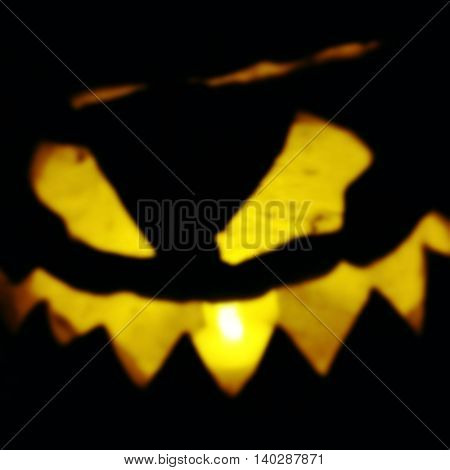 defocused image of a menacing Halloween jack o lantern glowing in the dark toned with a retro vintage instagram filter app or action