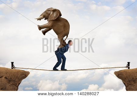 business challenge concept businessman carrying an elephant across a tightrope chasm