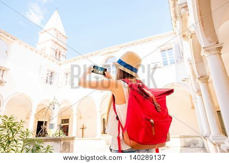 Young female traveler photographing with phone old monastery in Piran town. Traveling in Slovenia