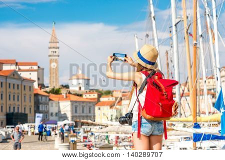 Young female traveler with hat and backpack photographing with phone piran town. Traveling in Slovenia
