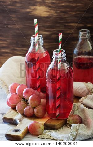 Fresh grape juice in a glass bottle and ripe berries on the table. Rustic style. Health and diet food. Selective focus
