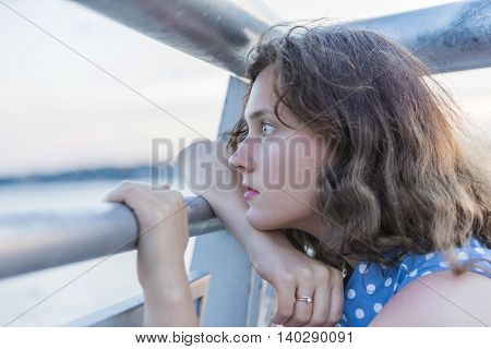 Profile of young woman with rings on finger thinking and looking through railing at river