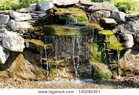 Landscapers waterfall shinning on a beautiful summer day