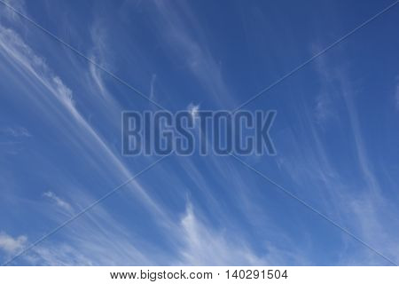 a blue summer sky background with white wispy clouds