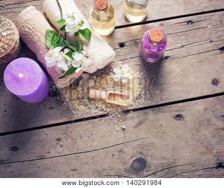 Spa or wellness setting. Beige sea salt bottles with aroma oil towels candle and flowers on white wooden background. Selective focus. Place for text. Toned image.