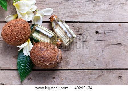Coconuts and coconut oil on vintage wooden background. Selective focus is on nuts. Flat lay. Natural organic spa products. Place for text. Toned image.