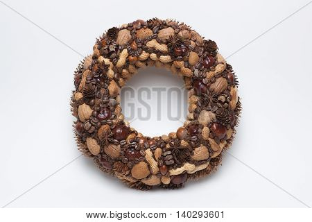 Decorative wreath made of nuts and pine cones isolated on white background