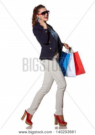 Woman With Shopping Bags Speaking On Mobile Phone And Walking