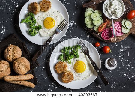 Fried eggs chicken meatballs vegetables and yogurt sauce on a dark background. Healthy lunch or snack