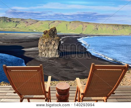 Rock in the sand. Cape Dirholaey in southern Iceland. On a coastal rock delivered comfortable wooden loungers