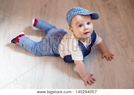 boy kid blonde in a cap and pants lying on the floor