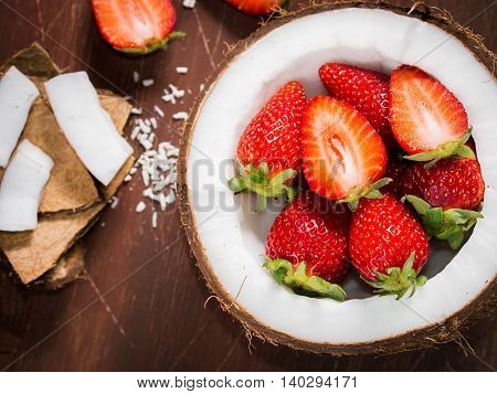 Coconut Shell With Strawberries On Rustic Wooden Background