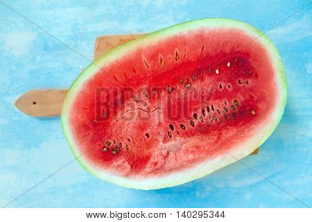 Watermelon cross section slice on rustic wooden table top view selective focus