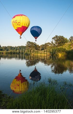 multicolored balloons flying in the sky over the lake